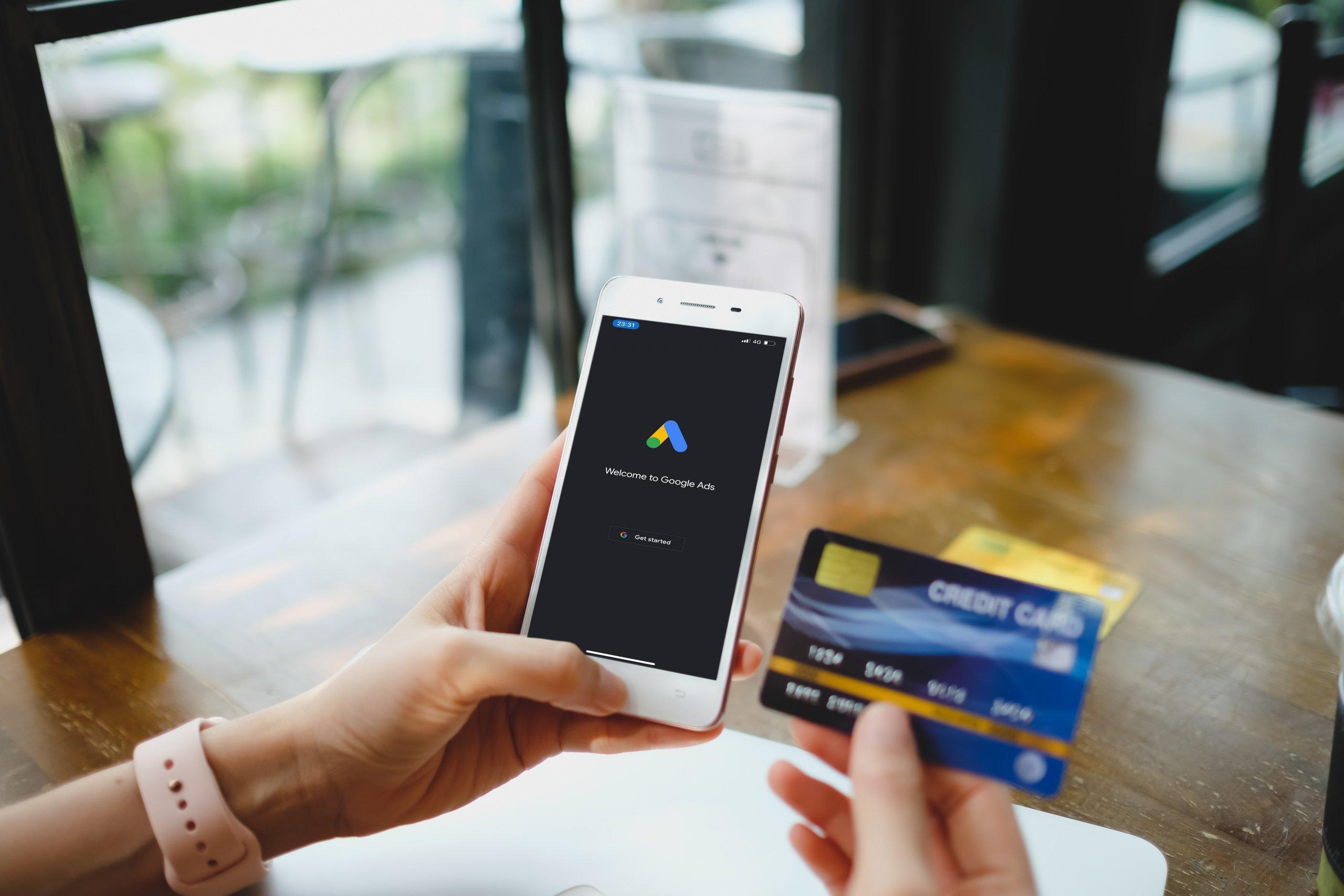 Mujer con tarjeta de crédito y google ads abierto en el teléfono móvil