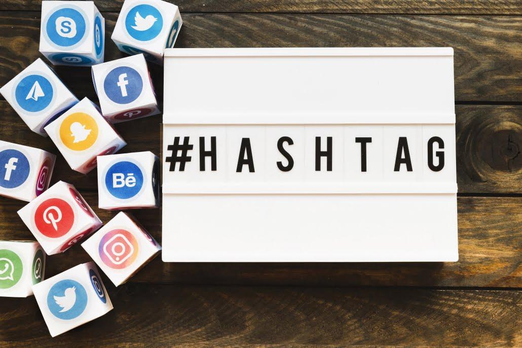 La palabra hashtag escrita en un cartel junto a los logos de varias redes sociales
