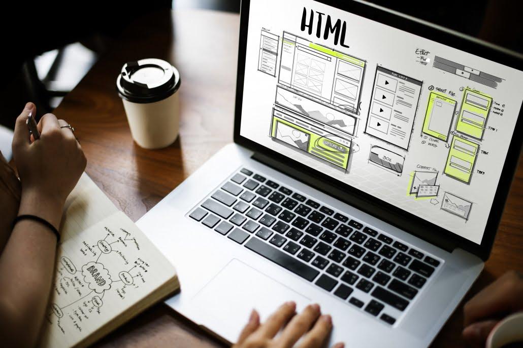 Imagen de una persona diseñando una web con HTML en su portátil.
