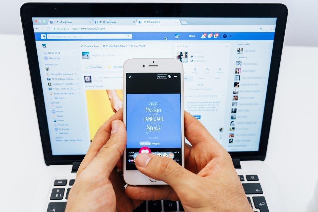 Persona utilizando Facebook en el móvil y en el ordenador portátil