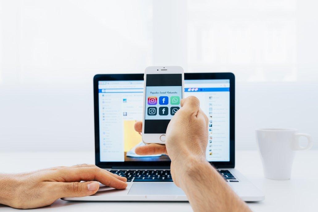 Persona utilizando las redes sociales en su ordenador portátil y en su móvil
