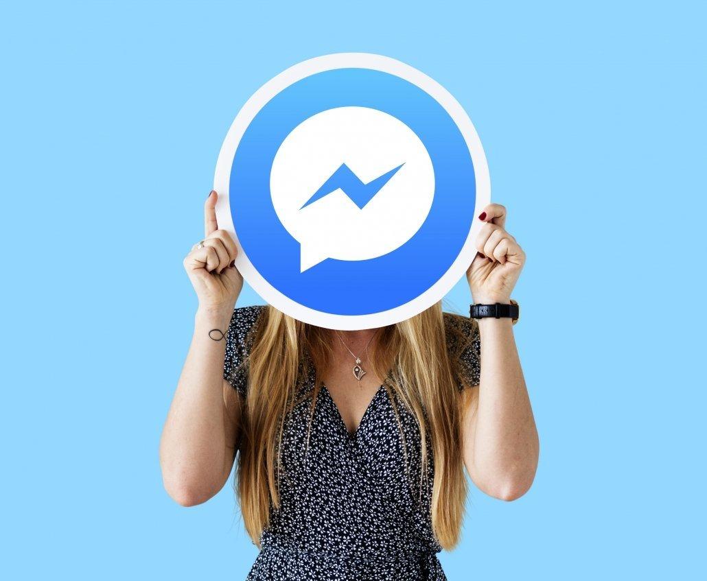 Mujer sujetando cartel con el logo de Facebook Messenger